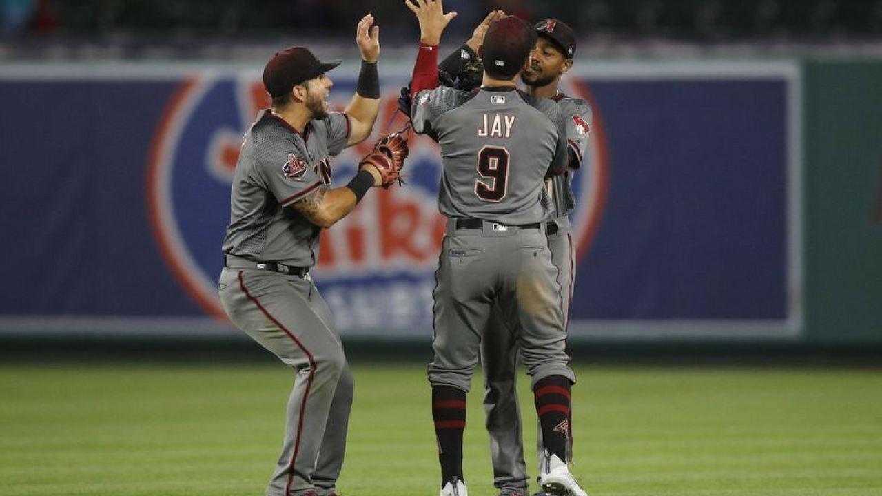 Arizona Diamondbacks' David Peralta, from left, Jon Jay and Jarrod Dyson celebrate the team's 7-4 win against the Los Angeles Angels in a baseball game, Monday, June 18, 2018, in Anaheim, Calif. (Source: AP Photo)