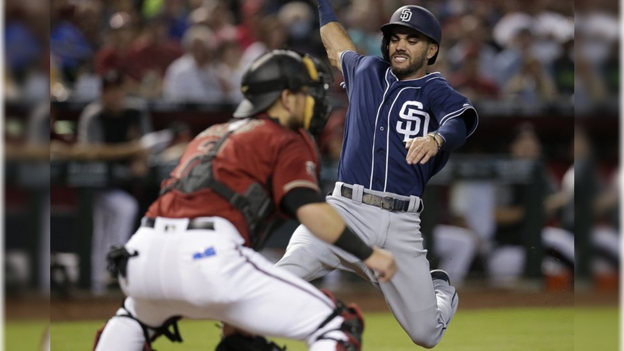 San Diego Padres' Carlos Asuaje, right, scores a run in the first inning on a double hit by Eric Hosmer during a baseball game against the Arizona Diamondbacks, Sunday, July 8, 2018, in Phoenix. (Source: AP Photo/Rick Scuteri)