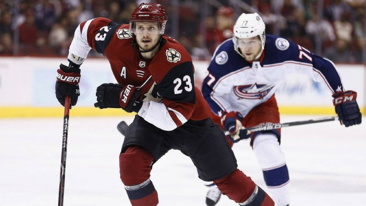FILE- Jan. 25, 2018, file photo, Arizona Coyotes defenseman Oliver Ekman-Larsson (23) and Columbus Blue Jackets right wing Josh Anderson (77) skate to the puck in Glendale, Ariz. Shane (AP Photo/Ross D. Franklin, File)