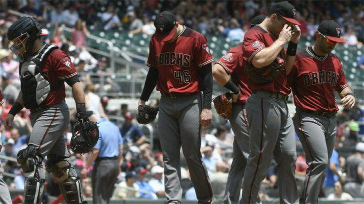 Arizona Diamondbacks starting pitcher Patrick Corbin, center, is visited on the mound after allowing three runs during the third inning of a baseball game against the Atlanta Braves, Sunday, July 15, 2018, in Atlanta. (Source: AP Photo/John Amis)
