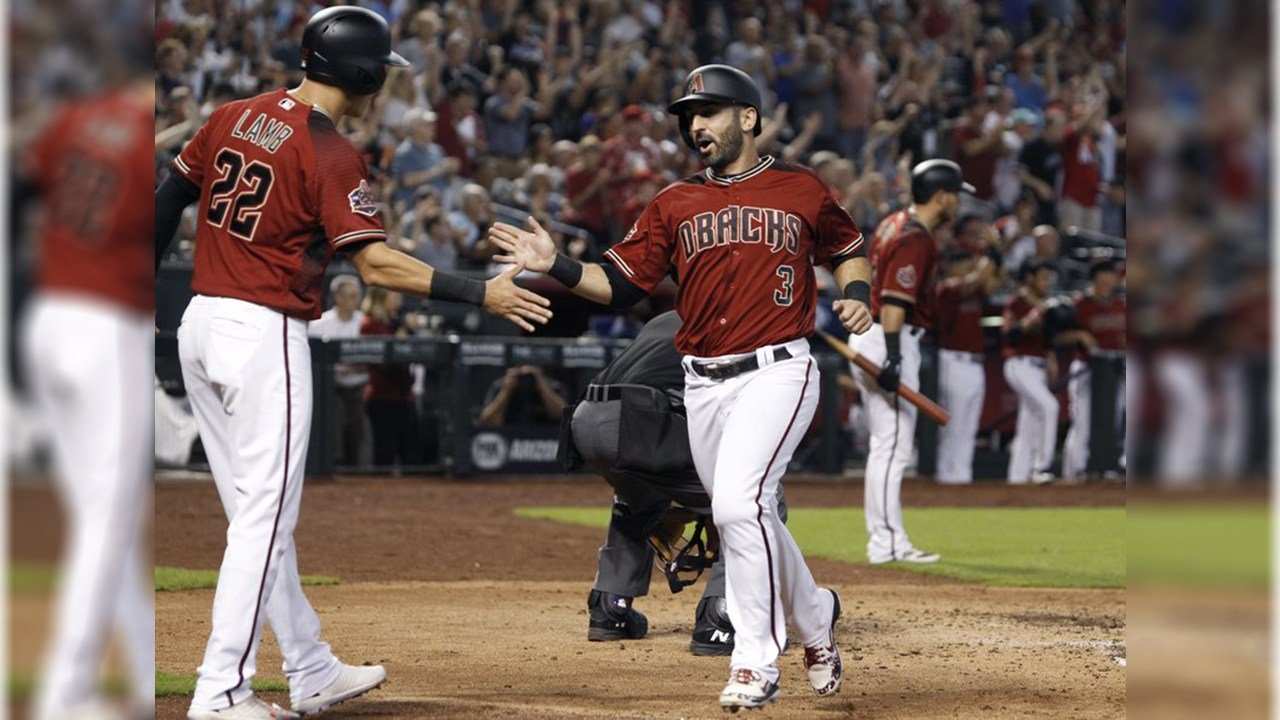 Diamondbacks' Daniel Descalso (3) is congratulated by Jake Lamb (22) after scoring a run against the Colorado Rockies on a triple by teammate Nick Ahmed during the fourth inning of a baseball game, Sunday, July 22, 2018, in Phoenix. (AP Photo/Ralph Freso)