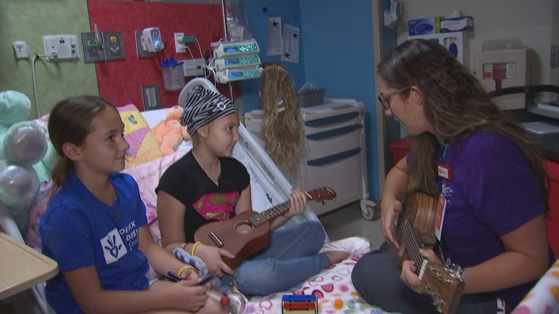 Music therapist Julie Renato teaches patient Hannah to play the ukulele. (Source: 3TV/CBS 5)