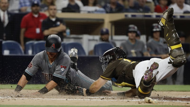 Diamondbacks' Jeff Mathis, left, scores from second base off an RBI-single by Jon Jay as San Diego Padres catcher Austin Hedges, right, is late with the tag during the third inning of a baseball game July 27, 2018, in San Diego. (AP Photo/Gregory Bull)