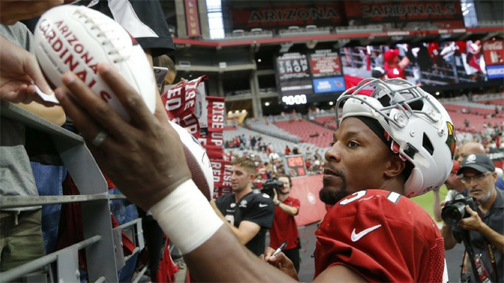 Arizona Cardinals running back David Johnson gives autographs to fans after an NFL football practice Saturday, Aug. 4, 2018, in Glendale, Ariz. (Source: AP Photo/Ross D. Franklin)