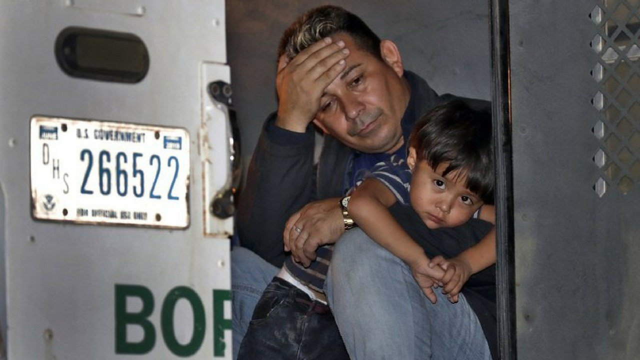 A father and his 3-year-old son are detained in the back of a U.S. Customs and Border Patrol vehicle Wednesday, July 18, 2018 in San Luis, Ariz. (AP Photo/Matt York)