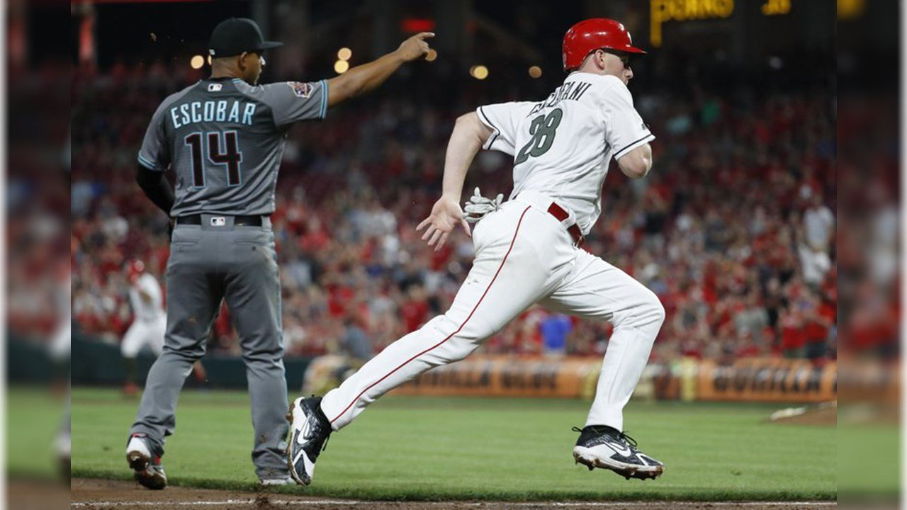 Cincinnati Reds' Anthony DeSclafani (28) runs home to score on a bunt single by Billy Hamilton off Diamondbacks starting pitcher Clay Buchholz and a throwing error by Buchholz during the seventh inning of a baseball game. (Source: AP Photo/John Minchillo)