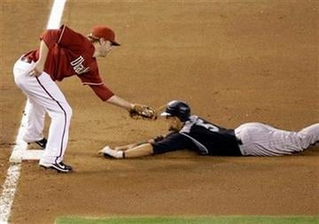 Arizona Diamondbacks third baseman Mark Reynolds, left, prepares to tag out Colorado Rockies' Carlos Gonzalez, right, in the eighth inning of a baseball game Sunday, Sept. 20, 2009, in Phoenix. (AP Photo/Paul Connors) By Paul Connors