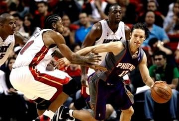 Phoenix Suns' Steve Nash (13) drives the ball between Miami Heat's Udonis Haslem (40) and Dwyane Wade (3) during  the fourth quarter of an NBA basketball game  in Miami, Tuesday, Nov. 3, 2009. The Suns won 104-96. (AP Photo/J Pat Carter) By J Pat Carter