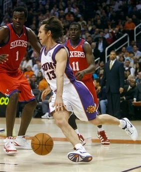 Phoenix Suns' Steve Nash (13) works around Philadelphia 76ers' Samuel Dalembert (1) and Jrue Holiday (11) during the third quarter of an NBA basketball game Wednesday, Feb. 24, 2010, in Phoenix. (AP Photo/Matt York) By Matt York
