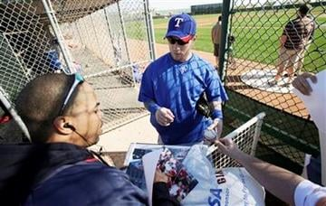 Texas Rangers center fielder Josh Hamilton signs autographs for fans during a baseball spring training workout, Tuesday, Feb. 23, 2010, in Surprise, Ariz. (AP Photo/Charlie Neibergall) By Charlie Neibergall