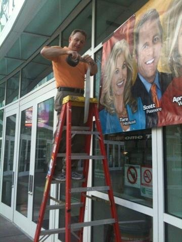 3TV Creative Services Manager hanging banners and prepping for the 3TV RUORNG Suns Rally By Content Creator