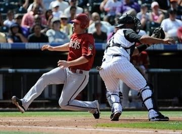 Arizona Diamondbacks' Ian Kennedy beats the tag by Colorado Rockies catcher Chris Iannetta to score during the third inning of an MLB baseball game in Denver, Sunday, Sept. 12, 2010. (AP Photo/Jack Dempsey) By Jack Dempsey