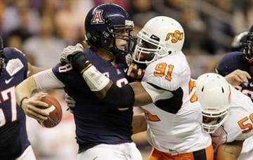 Arizona's Nick Foles (8) is sacked by Oklahoma State's Ugo Chinasa (91) during the first quarter of the Alamo Bowl NCAA college football game, Wednesday, Dec. 29, 2010, in San Antonio. (AP Photo/Eric Gay) By Eric Gay