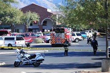 Emergency officials work at the scene of a shooting that authorities claim involved Rep. Gabrielle Giffords, D-Ariz., Saturday, Jan. 8, 2011, at a Safeway grocery store in Tucson, Ariz. (AP Photo/Chris Morrison) By Chris Morrison