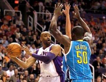 Phoenix Suns' Vince Carter, left, looks to pass as New Orleans Hornets' Emeka Okafor (50) defends during the first quarter of an NBA basketball game Sunday, Jan. 30, 2011, in Phoenix. (AP Photo/Ross D. Franklin) By Ross D. Franklin