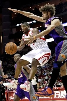 Houston Rockets' Kyle Lowry, left, looks to pass the ball as Phoenix Suns' Robin Lopez, right, defends during the third quarter of an NBA basketball game, Monday, March 14, 2011, in Houston. The Rockets beat the Suns 95-93. (AP Photo) By Natalie Rivers