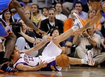 Phoenix Suns guard Steve Nash falls as Oklahoma City Thunder guard Thabo Sefolosha, right, of Switzerland, chases the loose ball during the first quarter of an NBA basketball game Wednesday, March 30, 2011, in Phoenix. (AP Photo/Matt York) By Matt York