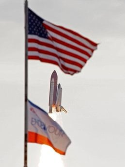 Space shuttle Endeavour flies past the US and mission flags after launch at Cape Canaveral, Fla., on Monday, May 16, 2011.  (AP Photo/John Raoux) By John Raoux