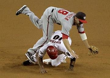 Arizona Diamondbacks' Justin Upton (10) is forced out as he up-ends Washington Nationals' Danny Espinosa during the fourth inning of a baseball game, Thursday, June 2, 2011, in Phoenix. (AP Photo/Matt York) By Matt York