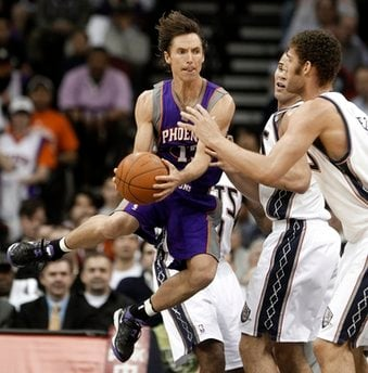 Phoenix Suns point guard Steve Nash, left, makes a pass as he faces New Jersey Nets' Kris Humphries, center, and Brook Lopez during the first quarter of an NBA basketball game, Monday, Feb. 28, 2011, in Newark, N.J. (AP Photo/Julio Cortez) By Julio Cortez
