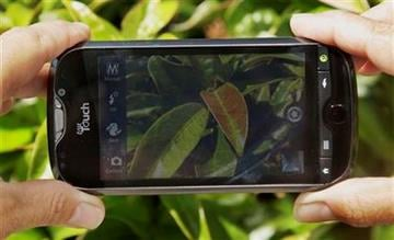 An Associated Press reporter demonstrates the camera on the HTC myTouch 4G Slide smartphone from T-Mobile during a product review in San Francisco, Wednesday, Aug. 10, 2011. (AP Photo/Jeff Chiu) By Jeff Chiu