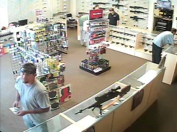 This man was with the suspect when he walked into the shop. The suspect can be seen leaning on a counter on the right side of the photo. By Catherine Holland
