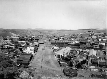 """Nogales, Santa Cruz County, Arizona. Showing boundary line between Arizona and Mexico."""" General view of center of town from hillside, looking west along International Street, ca. 1898~99 By Belo Content KTVK"""