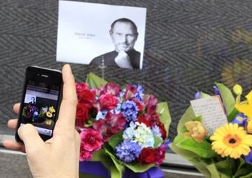 A man uses his iPhone to photograph flowers and a photocopy image of Steve Jobs that is placed at the entrance at the Apple Store in Sydney, Thursday, Oct. 6, 2011. By Catherine Holland