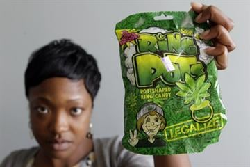 "In an Oct. 6, 2011 photo, Felicia Williams, Community Liason for Buffalo City Council member Darius Pridgen, holds a package of ""Ring Pots"" candy in Buffalo, N.Y. By Catherine Holland"
