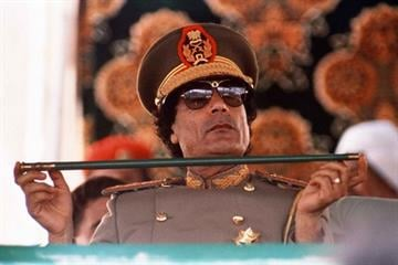 In this Sept. 1, 1987 file photo, Libyan leader Col. Moammar Gadhafi, holds a baton as he sits to review Libyan troops during the 18th anniversary celebration of Libya's revolution in Tripoli. By Catherine Holland