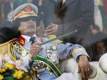 In this Tuesday, Sept. 1, 2009 file photo, Libyan leader Moammar Gadhafi gestures with a green cane as he takes his seat behind bulletproof glass for a military parade in Green Square, Tripoli, Libya. By Catherine Holland