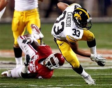 Iowa running back Jordan Canzeri (33) stays upright after being hit by Oklahoma defensive back Tony Jefferson during the first half of the Insight Bowl NCAA college football game, Friday, Dec. 30, 2011, in Tempe, Ariz. (AP Photo/Matt York) By Matt York