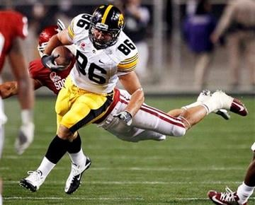 Iowa tight end C.J. Fiedorowicz (86) eludes the reach of Oklahoma linebacker Travis Lewis during the first half of the Insight Bowl NCAA college football game, Friday, Dec. 30, 2011, in Tempe, Ariz. (AP Photo/Matt York) By Matt York