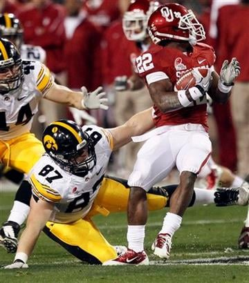 Oklahoma running back Roy Finch (22) spins around the reach of Iowa defensive lineman Thomas Nardo (87) during the first half of the Insight Bowl NCAA college football game, Friday, Dec. 30, 2011, in Tempe, Ariz. (AP Photo/Matt York) By Matt York