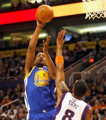 Golden State Warriors forward Dominic McGuire, left, shoots over Phoenix Suns center Channing Frye  during the first quarter of an NBA basketball game on Monday, Jan. 2, 2012, in Phoenix.  (AP Photo/Rick Scuteri) By Rick Scuteri