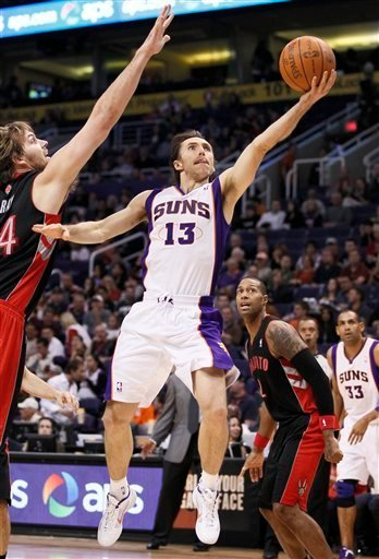 Phoenix Suns' Steve Nash (13) shoots past Toronto Raptors' Aaron Gray during the second half of an NBA basketball game, Tuesday, Jan. 24, 2012, in Phoenix. The Raptors won 99-96. (AP Photo/Matt York) By Matt York