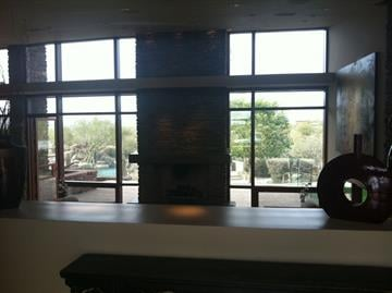 A fireplace and floor-to-ceiling windows showing of the desert view By Mike Gertzman
