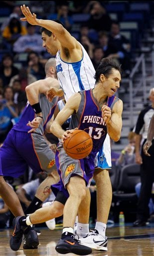 Phoenix Suns guard Steve Nash (13) cuts around New Orleans Hornets forward Gustavo Ayon in the first half of an NBA basketball game in New Orleans, Wednesday, Feb. 1, 2012. The Suns won 120-103. (AP Photo/Bill Haber) By Bill Haber