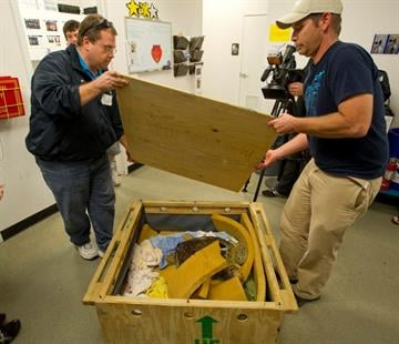 SEA LIFE Arizona Curator Dirk and Aquarist Greg open Ziva's travel crate. By Catherine Holland