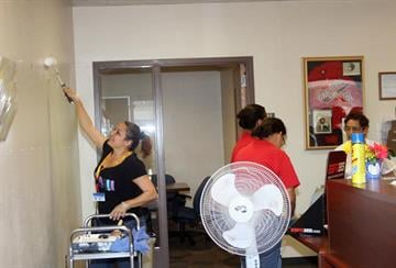 Cleaning crews/volunteers paint the inside of the administration building. By Jennifer Thomas