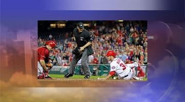 Washington Nationals' Bryce Harper slides across home plate. By Jennifer Thomas