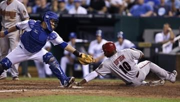 KANSAS CITY, MO - MAY 18:  Justin Upton #10 of the Arizona Diamondbacks slides safely into home past Humberto Quintero #33 of the Kansas City Royals at Kauffman Stadium May 18, 2012 in Kansas City, Missouri. (Photo by Ed Zurga/Getty Images) By Ed Zurga