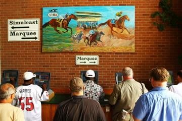 ELMONT, NY - JUNE 09:  Patrons bet on a horse race during the 144th running of the Belmont Stakes at Belmont Park on June 9, 2012 in Elmont, New York.  (Photo by Al Bello/Getty Images) By Al Bello