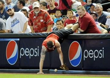 PHOENIX, AZ - JUNE 20:  Fans try to get a foul ball during a game between the Seattle Mariners and Arizona Diamondbacks at Chase Field on June 20, 2012 in Phoenix, Arizona.  (Photo by Norm Hall/Getty Images) By Norm Hall