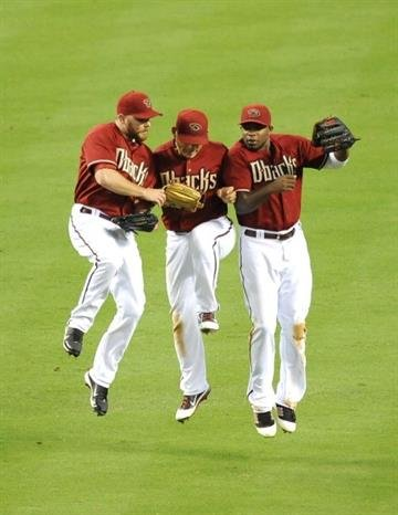 PHOENIX, AZ - JUNE 24: Jason Kubel #13, Gerardo Parra #8 and Justin Upton #10 of the Arizona Diamondbacks celebrate a 5-1 win against the Chicago Cubs at Chase Field on June 24, 2012 in Phoenix, Arizona.  (Photo by Norm Hall/Getty Images) By Norm Hall