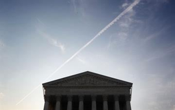 WASHINGTON, DC - JUNE 25:  A plane flies over the U.S. Supreme Court on June 25, 2012 in Washington, DC. The Supreme Court is expected to hand down its ruling on the Healthcare Reform Law soon.  (Photo by Alex Wong/Getty Images) By Alex Wong