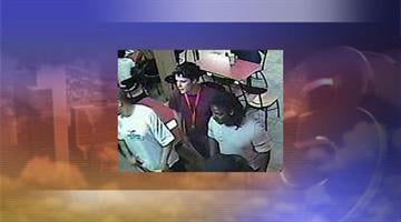 The suspect's associate is wearing a maroon shirt and blue jeans in this picture. By Jennifer Thomas
