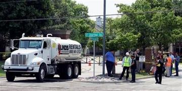 Emergency crews and police officials stand near wreckage Friday, July 6, 2012, in Northbrook, Ill., from a train derailment and bridge collapse that killed two people near the Northbrook-Glenview border, on Wednesday. (AP Photo/Nam Y. Huh) By Nam Y. Huh