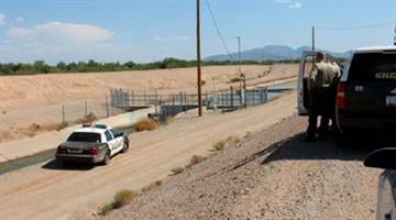 Investigators on the scene of where a man was found floating in a rural irrigation canal outside Maricopa on Aug. 9. By Jennifer Thomas