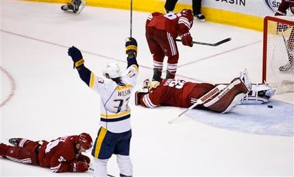 Nashville Predators' Colin Wilson (33) celebrates a game-winning goal by teammate James Neal as Arizona Coyotes' Louis Domingue, right, Klas Dahlbeck, left, of Sweden, and Mark Arcobello, top, react during overtime of an NHL hockey game Monday, March 9, 2